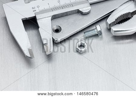 Vernier Caliper And Pliers On Scratched Metallic Background