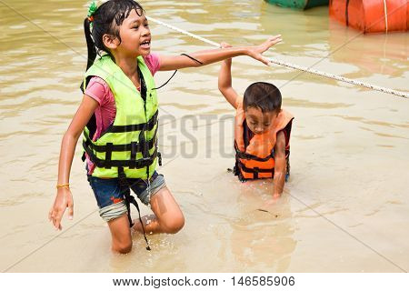 Two kids with life jacket playing waterswater safety ware concept