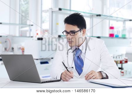 Picture of a male medical doctor writing prescription on the table while looking at the laptop in the laboratory