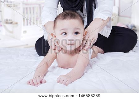 Close up of mother hands massaging baby back in the bedroom at home