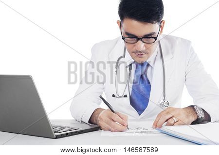 Close up of a male professional doctor writing a prescription on the paper with laptop on desk