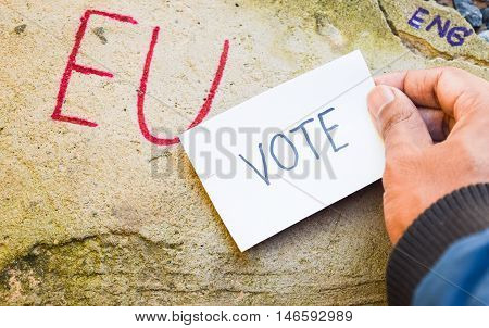 Brexit UK EU referendum concept with word UN and Eng and vote on hand on stone wall