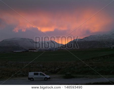 A White Van on a Mountain Road under the Beautiful Evening Sky of Iceland