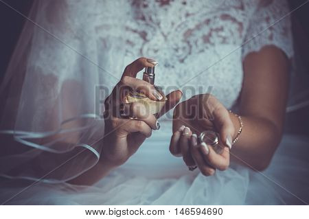 Hands close up. bride applying perfume on her wrist