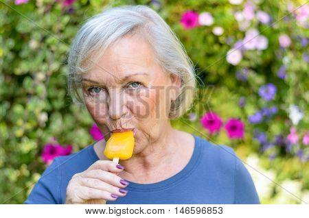 Elderly Woman Enjoying A Refreshing Iced Lolly