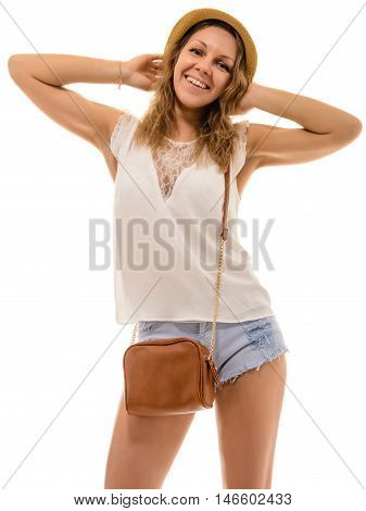 Cheerful young attractive girl in a straw hat and denim shorts with a small bag over his shoulder is holding up his hands behind his head isolated on white.