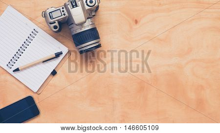 Top view of camera with notebookpen and mobilephone on wooden table background.
