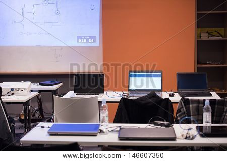 empty it classroom with program code on projector screen and modern laptop computers on table