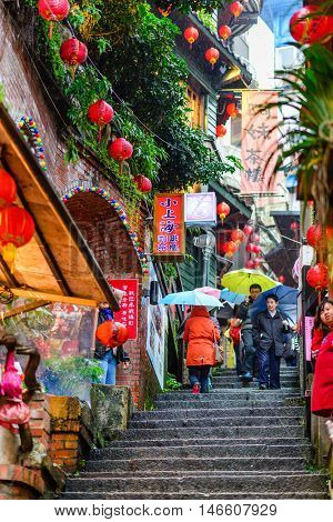 JIUFEN, TAIWAN - JANUARY 17, 2013: Tourists walk down famed steps in Jiufen. A gold mining town developed under Japanese rule, the city now attracts visitors for its nostalgic scenery.
