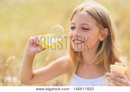 Joyful girl is blowing soap bubbles with enjoyment. She is standing on field and laughing