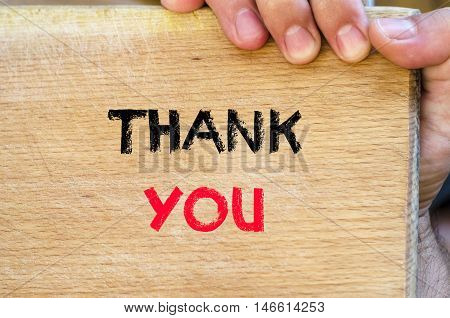 Human hand over wooden background and thank you text concept
