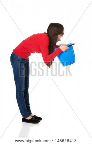 Young woman vomiting to bucket.