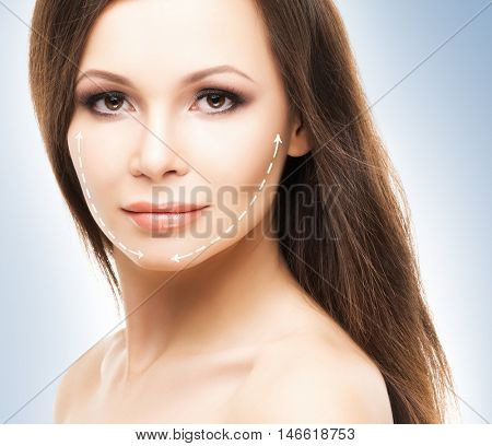 Spa portrait of attractive, young and healthy woman with arrows on her face. Plastic surgery treatment, medicine and skin care concept.