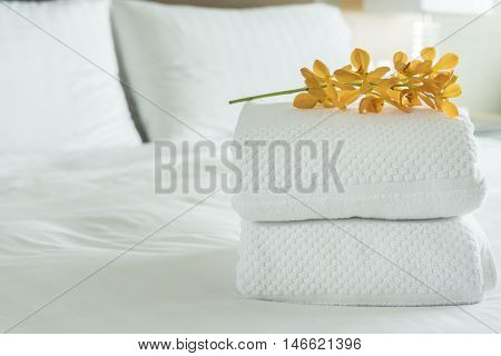 Close up Fresh white Towel with flowers placed on the inside of the hotel room.