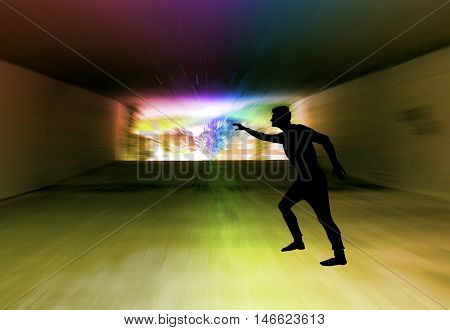 Silhouette of a man in a dark tunnel with a spectral light. Light at the end of dark tunnel and boy showing to the exit