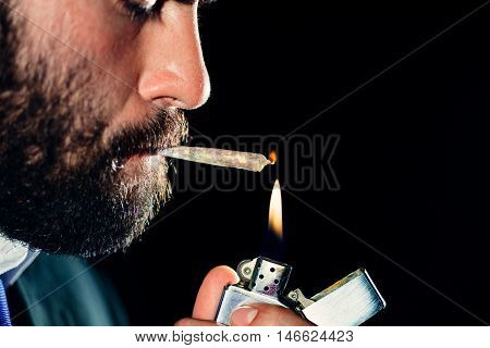 Man lighting and smoking a marijuana joint