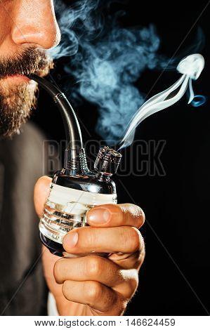 Man smoking marijuana using a glass pipe