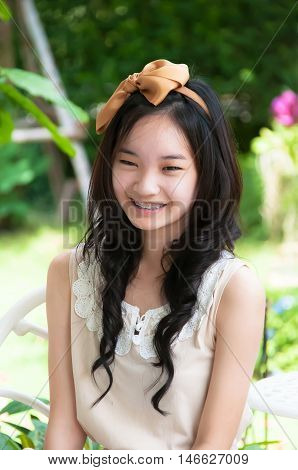 Outdoor portrait of attractive young asian chinese woman smiling in white dress