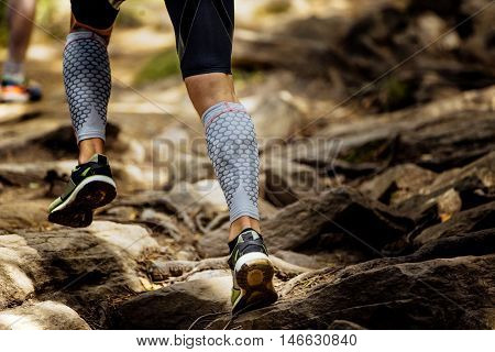 marathon runner running rocks in mountain. closeup of legs compression socks and shoes