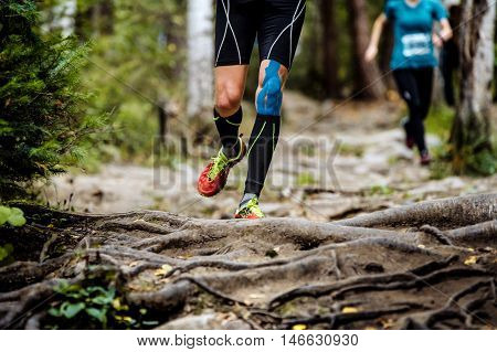 running marathon runner in forest. legs in compression socks knee taping