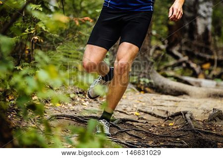running man marathon runner in woods over tree roots. tense muscles in legs