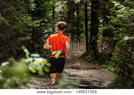 back male runner marathon runner running in forest. water bottle belt