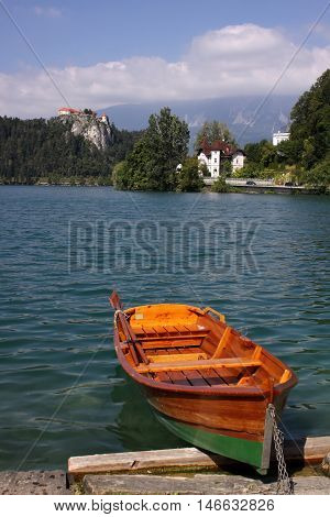 A colourful rowboat along the shore of Lake Bled with Bled Castle in the distance