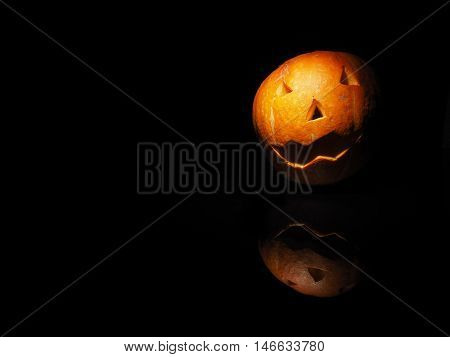 Halloween pumpkin on black background with reflection.