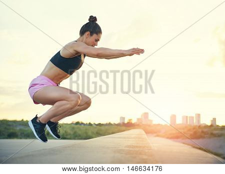 Healthy fit young woman doing crossfit exercises leaping on and off a low stone wall at the side of a promenade with the rising sun and cityscape in the distance