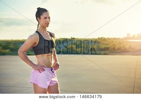 Toned healthy athletic young woman with a strong muscular body standing with her hands on her hips outdoors in the rising sun taking a break from her workout