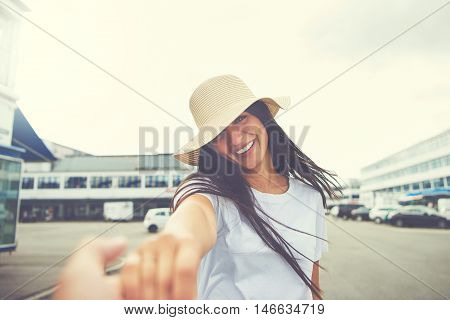 Woman with hat stretches hand toward camera and smiles while standing in parking lot of nearby shopping mall