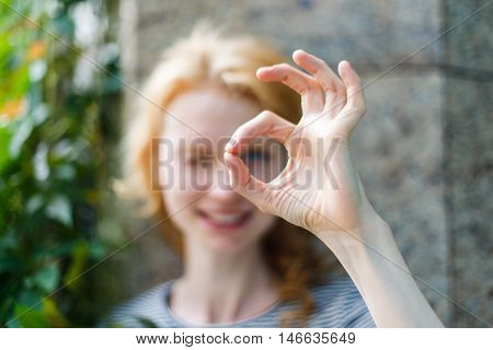 Closeup portrait outdoors of young woman looking through fingers showing OK sign. Focus on the hand