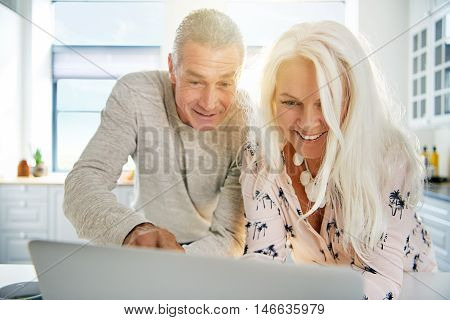 Excited senior couple looking at a laptop together in the kitchen pointing and smiling at something amusing on the screen