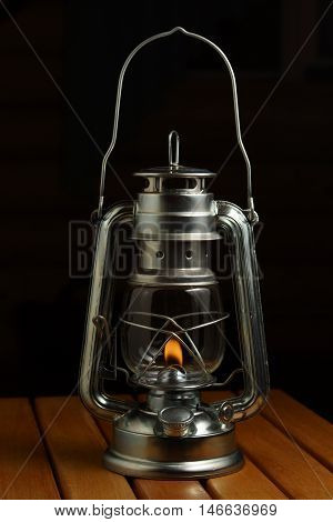 Kerosene lamp on the wood. Black background