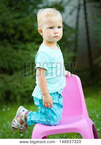 Portrait of a child knees on plastic chair, outdoor shoot