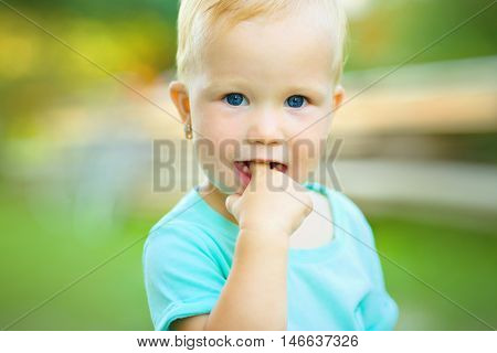 Portrait of a little girl with finger in her mouth, teething, outdoor shoot