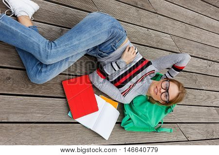 Girl lies among books and tablet on wooden floor in full growth.