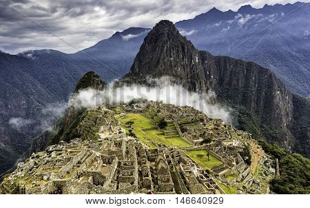 Ruins of Machu Picchu and Huayna Picchu covered by mystical cloud. Panoramic summer view from above.