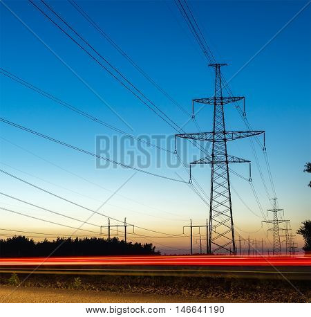 Pylons and electricity power lines at night with traffic lights
