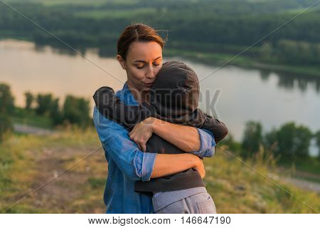 Mom hugging her son. Woman hugging a little boy outdoor. The concept of family in nature unity with nature gentle embrace. The landscape and the hill river and forest. Sun going down. August.