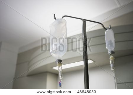 IV intravenous bag tube drip hang on silver metal stick therapy treatment to cue in hospital or clinic for patient