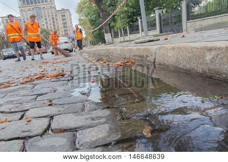 Kiev Ukraine - August 30 2016: Workers in orange vests sweep the pavement on the street Institutsuoy