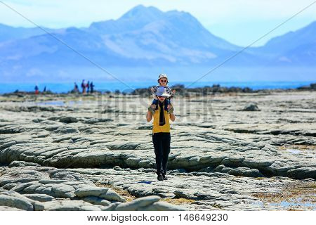 Young Woman With Small Daughter On Her Shoulders On Kaikoura Beach