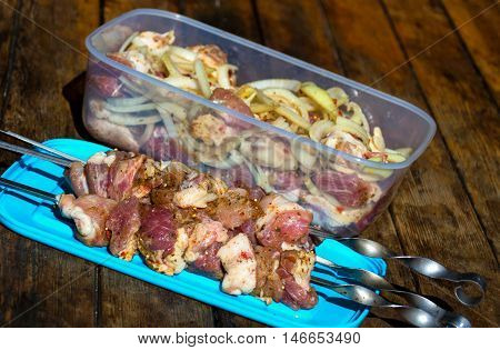 Raw pork meat, making kebab. Skewers ready for grilling and pieces of meat with onion and pepper in plastic food container on wooden table.