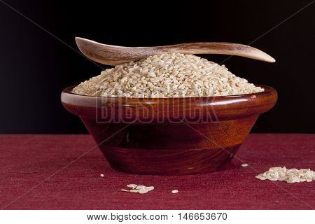 Bowl of brown rice with spoon. A bowl of raw uncooked brown rice with a wooden spoon.