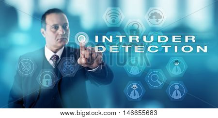 Experienced male information security director is pushing a virtual button to activate the term INTRUDER DETECTION onscreen. Computer security procedure metaphor and business concept.