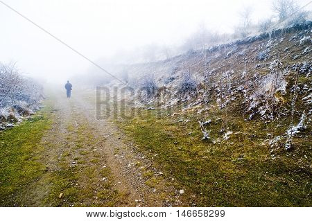 Person walking on misty pathway lonely walk