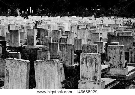 High contrast black and white view of headstones in an old crowded Jewish cemetery. poster