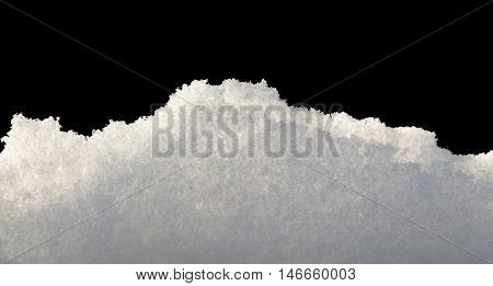 Closeup of backlighted snowbank isolated on black