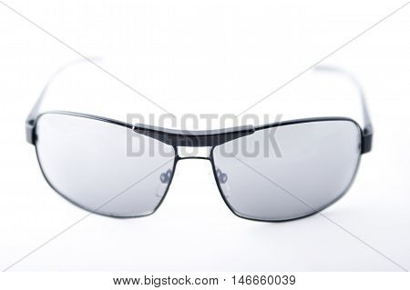 Closeup of black-rimmed sunglasses on white background.